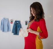 Andra o viitoare mamica de baietel, intr-o rochie rosie de gravide, sortand hainutele micutului